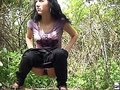 Unshaved brunette pissing in a forest