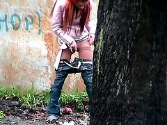 Red-hair girl filmed while doing a pee