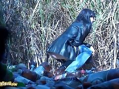 Brunette in jeans and jacket pees outside