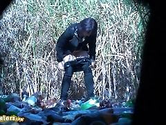 Woman in black pees on trash outdoors