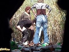 Women pee in the rushes near a trash pile