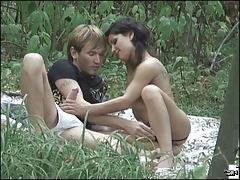 An oversexed couple doing the do in riverside grass