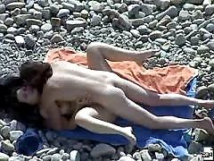 Brunette shows off assets on a sultry nude beach