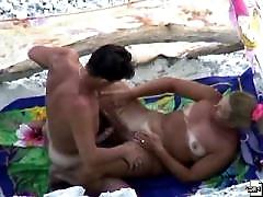 Voyeur filming of a nude girl having fun at the seaside