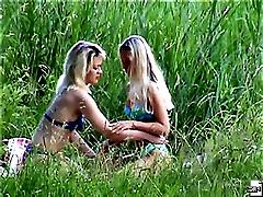 Two hot nude blondes make out near a lake