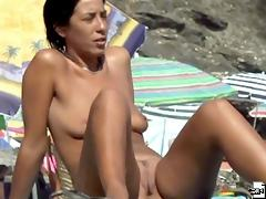 Spying on a tanned fully naked beauty having beach fun