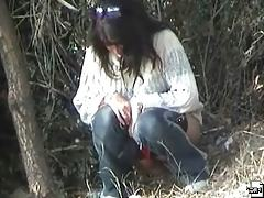 Brunette filmed while pissing in wood