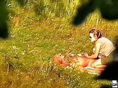 Bald hunk serviced by his girl in a field