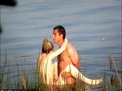 Tanned hung stud fucks a naked blonde in a lake